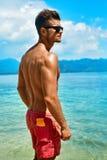 Sexy Mann, der mit Sunblock-Haut-Creme auf Sommer-Strand sich bräunt Lizenzfreies Stockbild