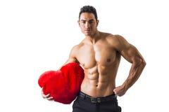 Sexy Mann mit den Muskeln, die rotes Herz-Spielzeug halten Stockfotografie