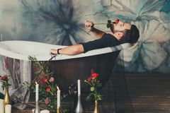 Sexy Mann mit einer Rose in der Wanne lizenzfreie stockfotografie