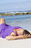 Sexy mature woman relaxing on beach. A pretty attractive looking mature woman wearing a purple dress at the beach, happily smiling and enjoying her life of Royalty Free Stock Photography