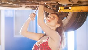 mechanic girl under the car with a spanner, looking up royalty free stock images