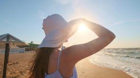 Sexy meisje dat het overzees bekijkt Een meisje in een hoed en glazen zoekt een blik naar de oceaan Verlaten één, verloren stock footage