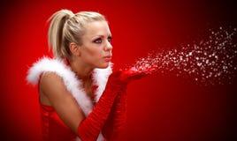 Sexy meisje in de blazende sneeuw van de santadoek van handen. Stock Fotografie