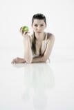 Sexy meisje die op de vloer met een appel liggen Royalty-vrije Stock Foto's