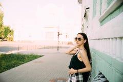 Sexy meisje in een T-shirt en korte borrels dichtbij het gebouw royalty-vrije stock foto