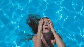 Sexy meisje in een witte bikini die in de pool zwemt stock footage