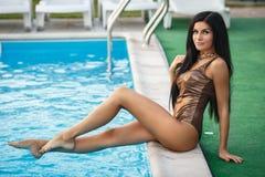 Sexy meisje in gouden zwempak op de pool Stock Afbeeldingen
