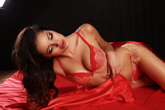 Sexy meisje met donker haar in rode lingerie die op zijdeblad liggen Stock Afbeeldingen