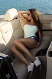 Sexy meisje met het donkere haar stellen in luxueuze cabriolet stock fotografie