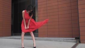 Sexy meisje in rode kledingsglimlachen Meisje met mooie benen in een windswept kleding de wind verstoort japon Langzame Motie stock videobeelden