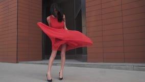 Sexy meisje in rode kledingsglimlachen Meisje met mooie benen in een windswept kleding Langzame Motie stock video