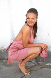 Sexy meisje in roze kledingssquati Royalty-vrije Stock Foto's