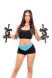 Sexy meisje in sportkleding die met twee barbells uitoefenen Royalty-vrije Stock Fotografie