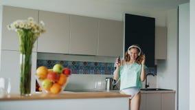 Sexy meisje in t-shirt die en in keuken zingen dansen Gelukkige vrouw in ondergoed stock videobeelden