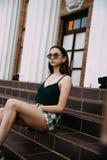 Sexy meisje in zonnebrilt-shirt en korte borrels dichtbij de kolommen royalty-vrije stock fotografie