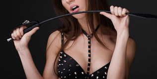 Sexy meisje in zwart spiked bustehouderspel met zweep Stock Afbeelding