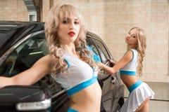 Sexy meisjes in de stijl van Formule 1 het stellen bij carwash stock foto
