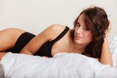 Sexy meisjes luie vrouw in ondergoed die op het bed liggen Stock Afbeelding