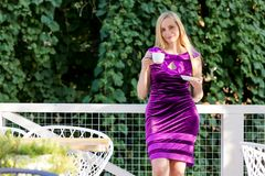 Menopause woman happy blonde middle age nature summer long hair sunlight fifty plus 50 pink dress clothing cup coffee royalty free stock images