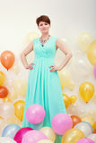 Sexy middle-aged model posing in turquoise dress Stock Photos
