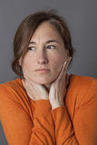 Middle aged woman touching her face for relaxing wellness. Middle aged woman with orange sweater touching her face for wellness and relaxation looking away or stock photography