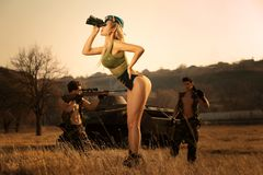 Sexy militair meisje met verrekijkers die iets, op de hooglandenachtergrond zoeken met sterke bewapende militairen stock fotografie