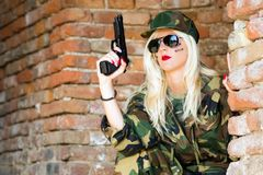 Sexy military woman with gun. The attractive sexy blond woman in military uniform is holding pistol on brick wall background Stock Photos