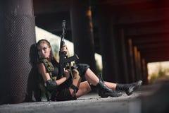 Sexy militärisches bewaffnetes Mädchen mit der Waffe, Scharfschütze Stockfotografie