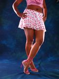 Miniskirt And Legs. Woman wearing a shirt exposing her bare navel, a white and pink miniskirt, and pink heels. Her hands are resting on her hips and her legs stock images