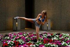Sexy mixed-martial arts (MMA) woman kicking Stock Photo