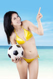 Sexy model with a ball pointing at copyspace Stock Photo