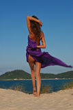 model on beach with purple sarong Stock Photos