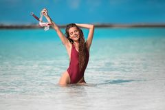 Sexy model on Beach vacation. Happy fun girl holding snorkel scuba mask standing in ocean water. Maldives summer. Young woman stock images