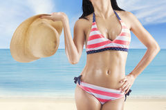 Sexy model with bikini and hat at shore Royalty Free Stock Image