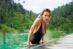 Model in black swimsuit posing in pool Royalty Free Stock Photography