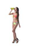 Sexy model in bright bikini drinks protein shake Stock Images