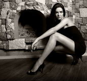 Sexy model in dress near fireplace Stock Photography