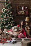 Sexy model dressed as Santa with a black crown near a Christmas tree holding a bear Stock Photography