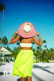 Sexy model girl  in colorful cloth and sunhat behind blue beach Stock Image