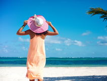 Sexy model girl  in colorful cloth and sunhat behind blue beach Stock Photo
