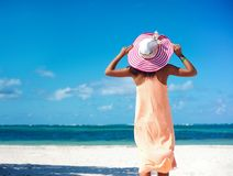Sexy model girl  in colorful cloth and sunhat behind blue beach Stock Photos