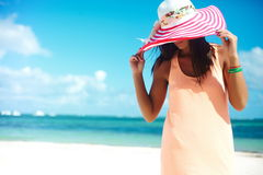 Sexy model girl  in colorful cloth and sunhat behind blue beach Royalty Free Stock Photos
