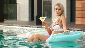 Sexy model het drinken cocktail op opblaasbare matras in pool stock footage
