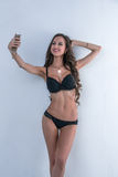 Sexy model in lingerie doing selfie on smartphone Royalty Free Stock Image