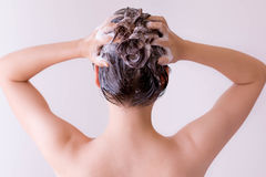 Model massaging shampoo into her hair, closeup profile from the back. Pink color theme. Woman shampooing hair. Fashion Stock Photography