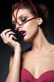 Sexy model met maniermake-up, ongebruikelijke gezichts bijkomende en donkere druiven royalty-vrije stock foto's