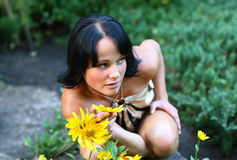 Sexy model in park with flowers Stock Image