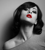 Sexy model with short hair style and red lips. Black and white. Sexy model with short hair style and red lips posing on dark background. Black and white Stock Photos