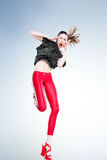 Sexy model with slim body dressed in red jumping and screaming in the studio Royalty Free Stock Photo