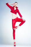 Sexy model with slim body dressed in red jumping in the studio Stock Photo